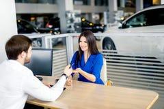 接受汽车钥匙的可爱的欧洲妇女从汽车经销处 库存图片