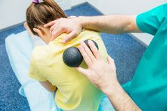 接受球按摩的物理疗法的妇女从治疗师A按摩医生对待在医疗offic的耐心` s胸部脊椎 免版税库存图片