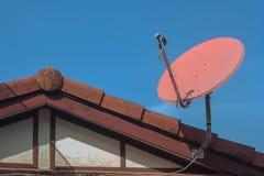 接受盘设置的数字式卫星电视在有蓝天的房子屋顶顶部在背景中 免版税库存照片