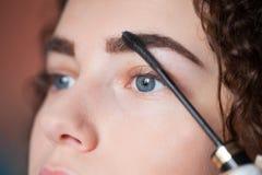 接受眼眉更正做法的少妇 眼眉染睫毛油 库存照片