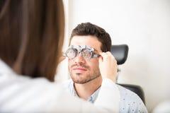接受眼睛考试的验光师通过试验框架在诊所 免版税库存照片