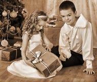 接受礼品的子项在圣诞树下 免版税库存图片