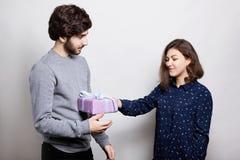 接受礼物的一名愉快的妇女从她的男朋友 一个时髦的男孩在给她的女朋友一个礼物为的偶然毛线衣穿戴了 库存照片
