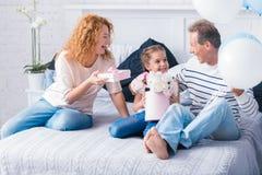 接受礼物的快乐的小女孩从她的祖父母 免版税库存照片