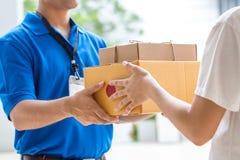 接受箱子的交付从送货员的妇女手 库存图片