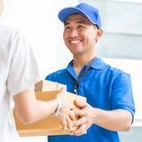 接受纸板箱的交付从送货员的妇女 免版税库存图片
