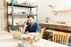 接受网上命令的陶瓷工使用手机和膝上型计算机 库存照片