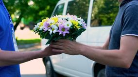 接受美丽的花束的人从送货人、命令和发货服务 库存照片
