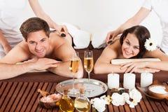 接受肩膀按摩的愉快的夫妇在秀丽温泉 免版税库存图片