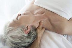 接受脖子按摩的资深妇女在温泉 免版税图库摄影