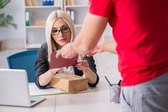接受邮件小包的妇女女实业家从传讯者 免版税图库摄影