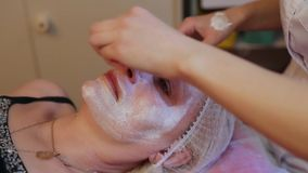 接受面部按摩的妇女在发廊 得到一种化妆治疗,特写镜头的妇女 美容师手在工作 股票录像