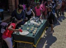 接受食物的可怜的小学生在施粥所 图库摄影
