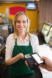 接受付款的女工画象通过NFC 免版税库存图片