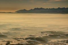 接合的Tatra峰顶在雾上海上升在日出在波兰 免版税库存照片