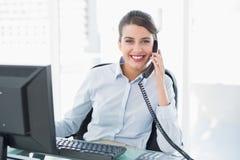 接听快乐的优等的棕色毛发的女实业家电话 库存照片