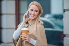 接在她的机动性的可爱的妇女一个电话 免版税库存照片