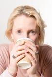 直接地注视白肤金发的妇女,当喝从一纸杯时 免版税库存照片