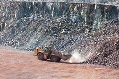 接地驾驶在一件地表矿山猎物的搬家工人 库存照片