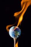 接地黏附与与火焰的高尔夫球 免版税库存图片