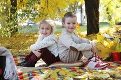 紧接坐在秋天树下的姐妹和兄弟 库存照片