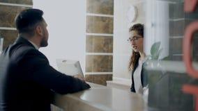 接待员女孩谈话与关于报到的到达的商人在招待会在旅馆里 事务、旅行和人们 股票视频