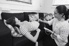 接生婆检查婴孩心跳和运动 图库摄影