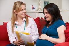 接生婆谈论医疗笔记与孕妇 免版税图库摄影