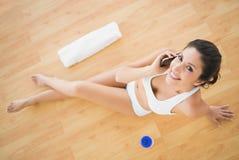 接电话的适合的愉快的妇女在她的看的锻炼期间来了 免版税图库摄影