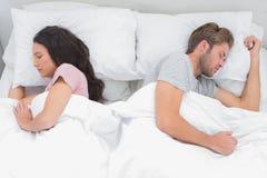 紧接睡觉在他们的床上的夫妇 免版税库存图片
