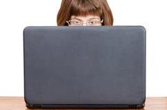 直接观点的戴眼镜的女孩从膝上型计算机读 图库摄影