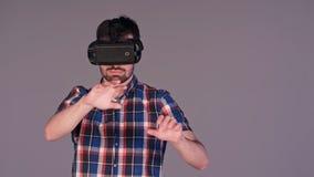 接触一个虚构的屏幕的虚拟现实玻璃的年轻人 库存图片