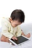 接触与片剂个人计算机的亚裔婴孩 库存照片