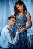 接触和听他美丽的迷人的怀孕的妻子的胃的英俊的丈夫的半身画象 免版税库存图片