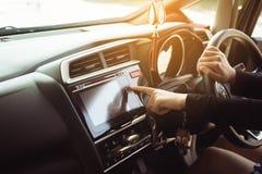 接触和打开汽车收音机系统,妇女司机的手指递拿着方向盘 库存照片