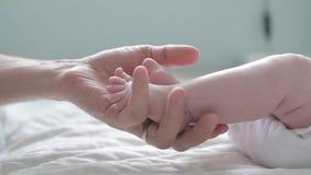 接触和计数他的新生儿的小趾的父亲 关闭 握新生儿脚的父母 愉快的父母身分 股票视频