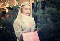 接触圣诞树的金发碧眼的女人 免版税图库摄影
