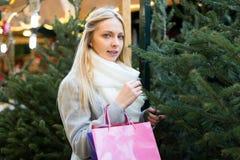 接触圣诞树的金发碧眼的女人 库存照片