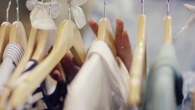 接触在一个机架的女性手接近的射击礼服在服装店 影视素材