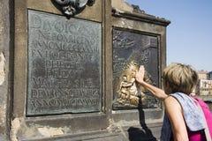 接触在匾的妇女在Nepomuk雕象的圣约翰下 库存图片