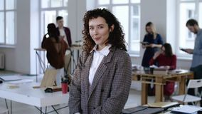 接触在正装,微笑的年轻欧洲女商人美丽的画象卷发愉快在现代办公室 股票视频
