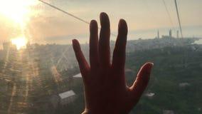 接触在缆索铁路的客舱里面的手玻璃,在日落,触感,旅行概念 股票录像