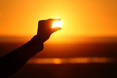 接触太阳的抽象手指在日落 免版税库存图片