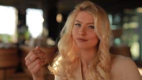接触头发的性感的可爱的妇女坐在看我的咖啡馆,挥动和卖弄风情 影视素材