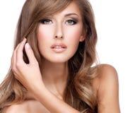 接触她华美的长的头发的一名美丽的妇女的特写镜头 图库摄影