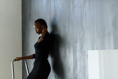 接触她在黑暗的演播室背景的相当非洲或黑人美国妇女侧视图厚实的褶 库存图片