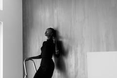 接触她在黑暗的演播室背景的相当非洲或黑人美国妇女黑和白色画象厚实的褶 图库摄影