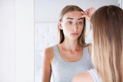 接触她的前额的妇女,当看在镜子在轻的屋子,秀丽概念,皱痕里时 图库摄影