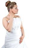 接触她的耳朵的白色婚礼礼服的妇女 免版税库存图片