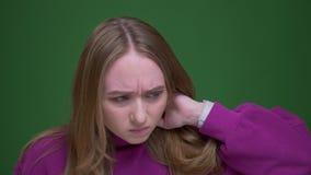 接触她的脖子的哀伤的姜女生有在绿色色度背景的喉咙痛 股票录像